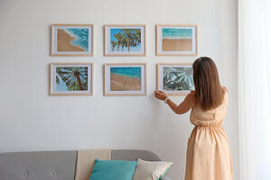 woman hanging pictures on a wall