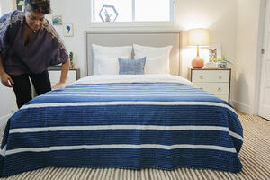 woman making bed_604760033