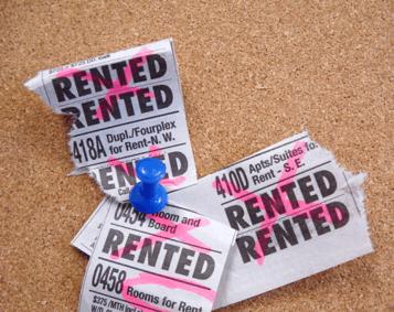 rental ads pinned to a cork board