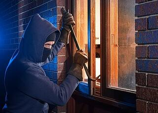 robber breaking in through a window