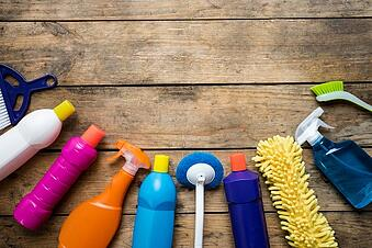 Cleaning supplies on a wooden background