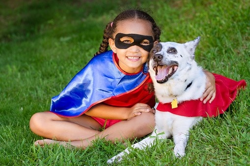 Girl and pet dog dressed as super heroes