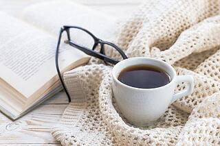 Cozy sweater, glasses, book and cup of coffee