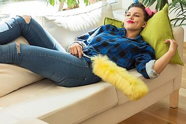 woman laying on couch with feather duster