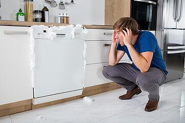 man shocked as foam comes out of dishwasher