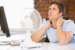 man_sitting_in_front_of_fan_and_computer