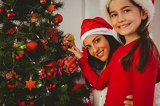 mother_and_daughter_hanging_ornaments_on_christmas_tree.jpg