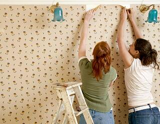 two girls removing wallpaper
