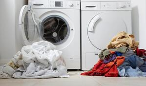 washer and dryer with piles of clothes