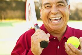 Man_smiling_holding_tennis_raquet_and_tennis_ball