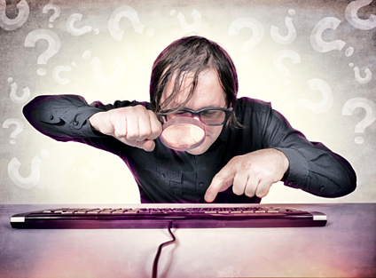 man searching at desk with magnifying glass and keyboard