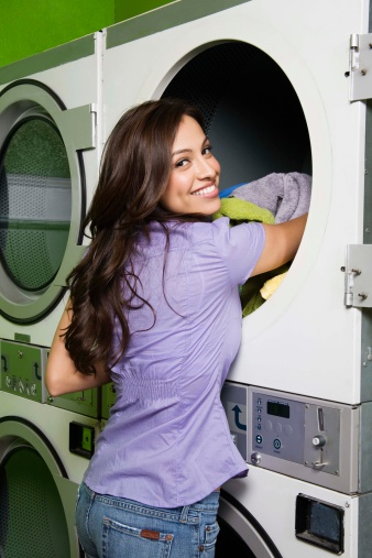woman_putitng_laundry_into_a_washer_at_a_laundromat