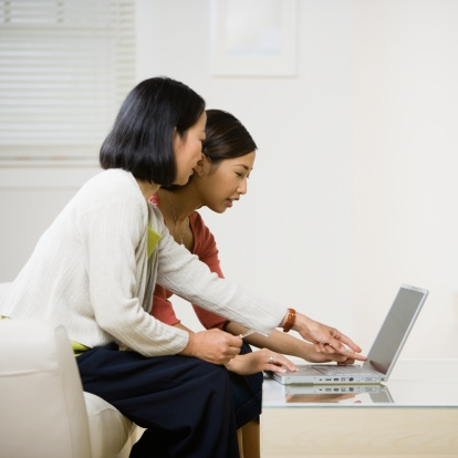 Two_woman_sitting_on_cough_apartment_searching_online-1